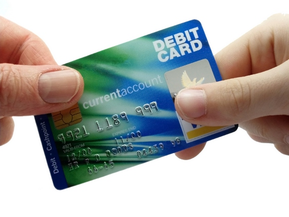 Male and femal hand holding a debit card