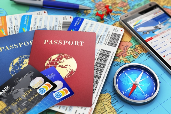 Passports, airline tickets, compass, mobile phone, and credit cards on a map.