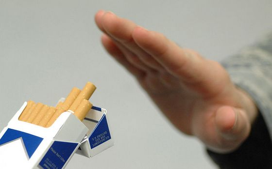 'No' handsign to a pack of cigarettes