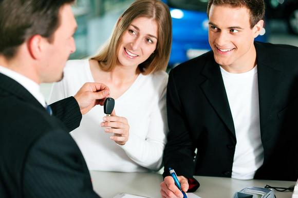 A couple getting key from a salesman
